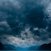 Fjord met donkere wolken en schittering op het water