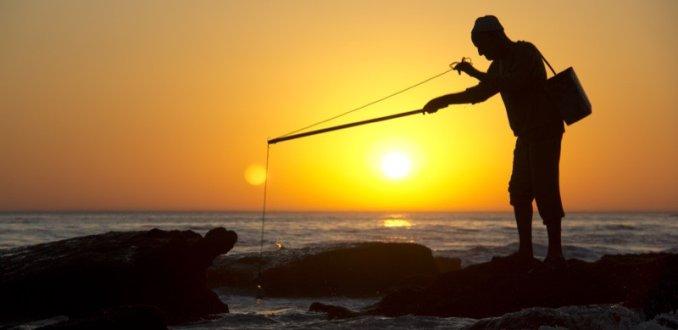 Man aan het vissen op inktvis, Taghazout, Marokko