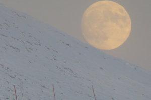 Op de Kongsfjordfjellet in winters Finnmark (noord Noorwegen) rolt de maan van de berghelling