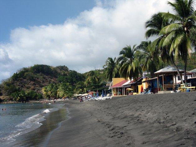 Groen eiland, zwart zand en blauwe lucht