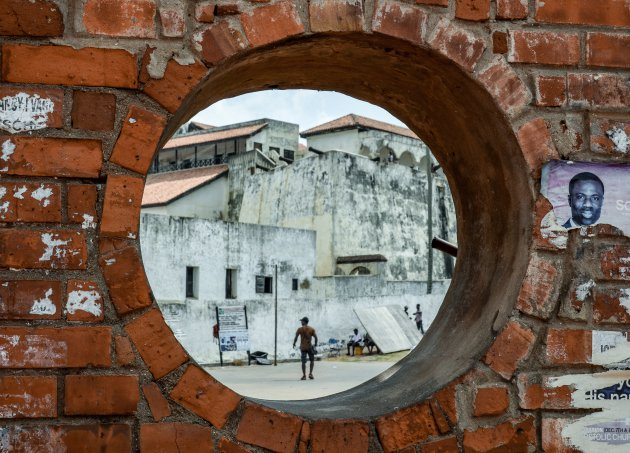 Elmina door een gat in de muur