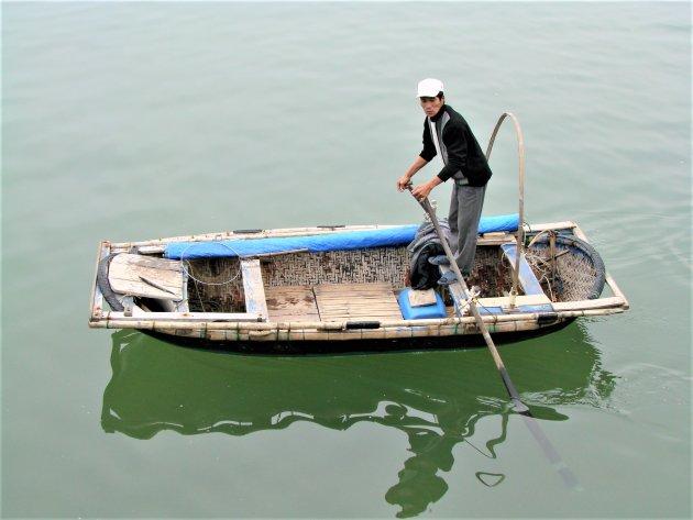Een visser op zijn bamboebootje.