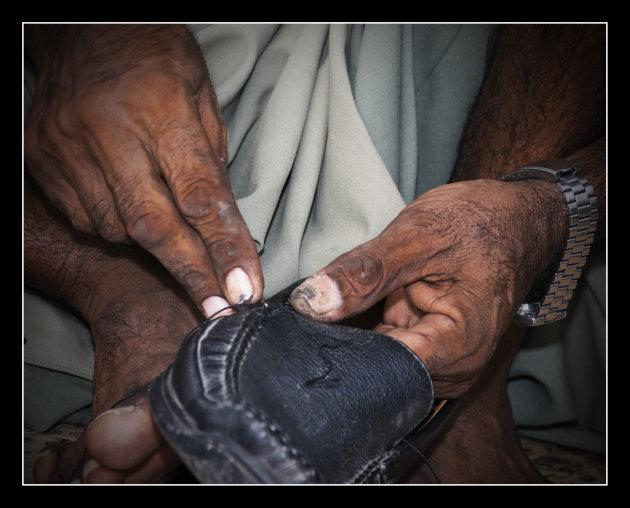 Handen van de schoenmaker