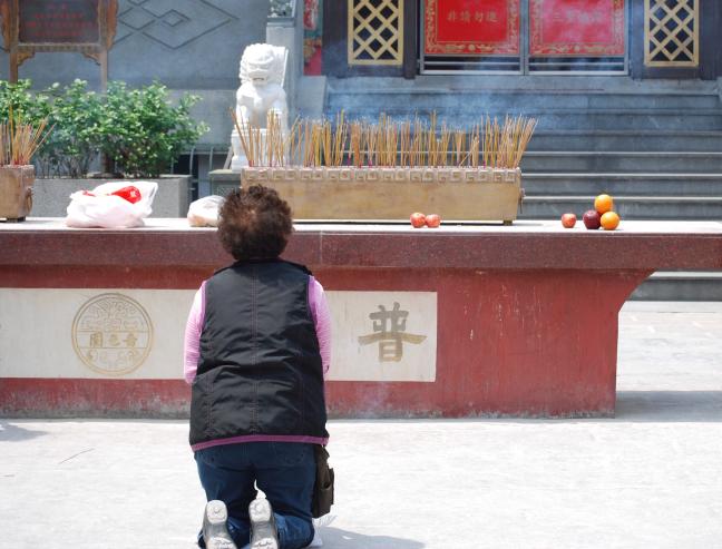 gehurkt voor Buddha