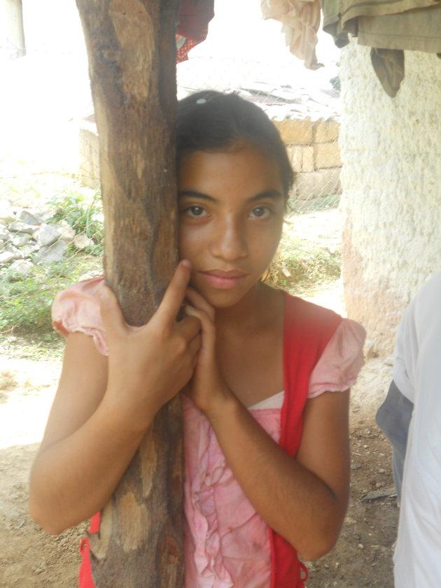 Op bezoek bij mensen thuis, in de gemeenschap El Espíritu, in de regio Florida, Noord-west Honduras. Meisje kijkt verlegen toe.