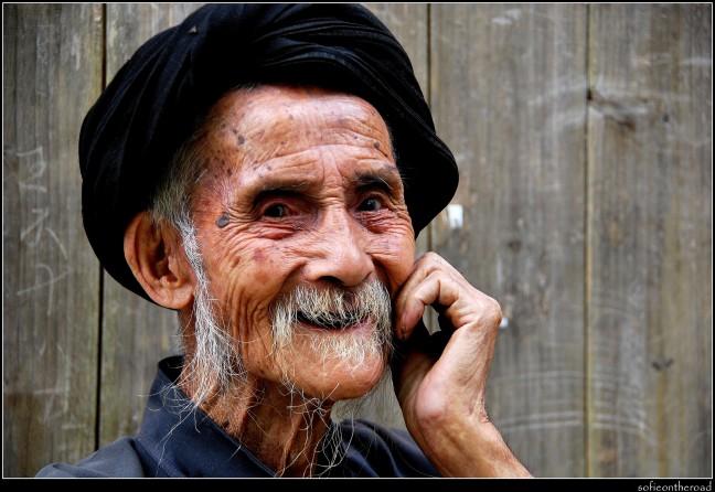 Oude man voor zijn huis in Yangdi