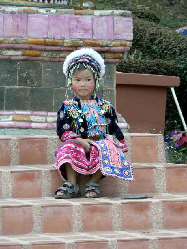 KInd van de Karen stam op de trappen van de Doi Suthep tempel