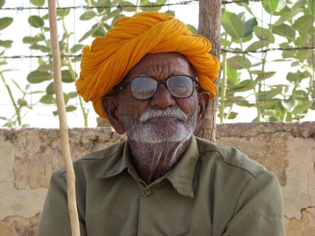 Oude man bij de ingang van een wegrestaurant onderweg naar Jaisalmer