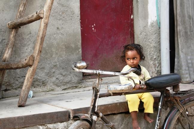 Kind in India zittend op muurtje