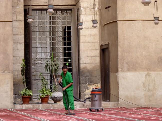 Deze man stofzuigt het tapijt in de Sultan Hassan moskee