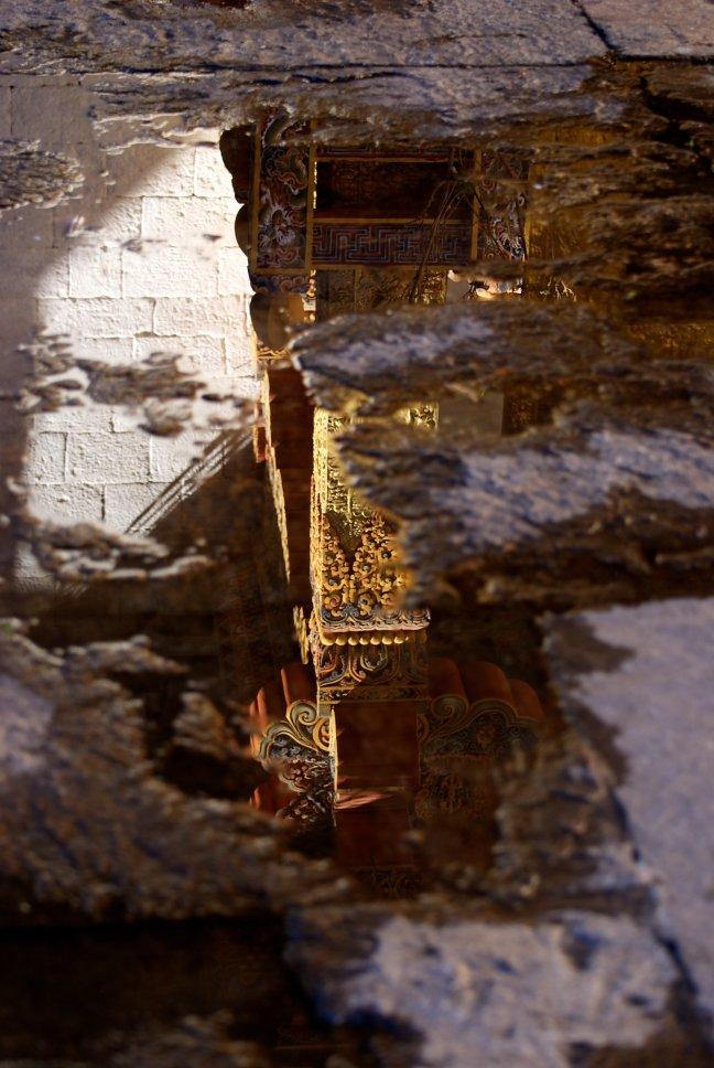 Reflectie van een onderdeel van een tempel in een plas.