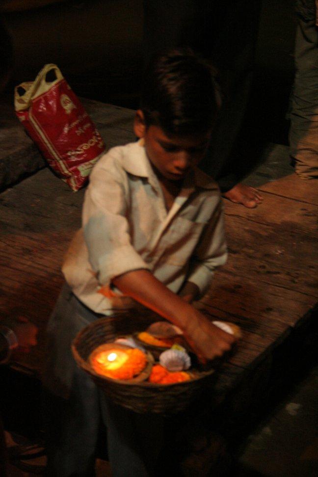 Verkopertje van offerkaarsjes in Varanasi