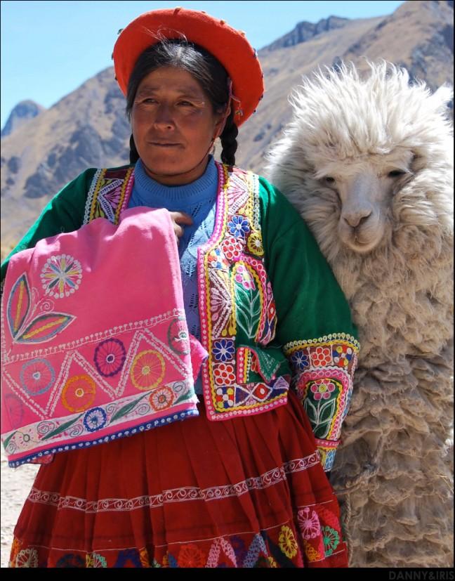 Vrouw in kleurige kleding met alpaca