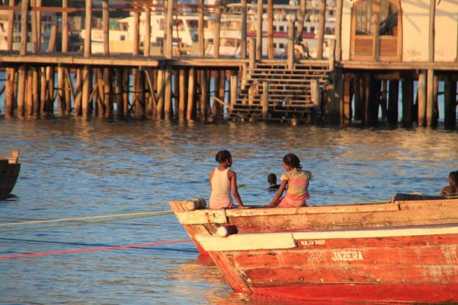 Meisjes zitten te kletsen op de rand van een boot in Stone Town