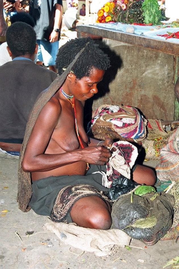 Papuavrouw een draagzak aan het maken.