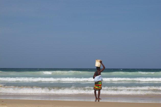 Vrouw met baby op de rug op strand van Dakar