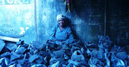 Vrouw achter tassen vol houtskool