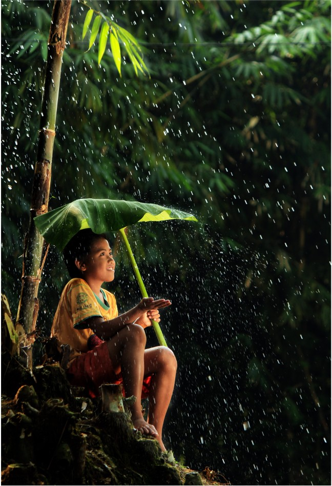 Dorpsjongen schuilt onder een bananenblad tegen de regen.