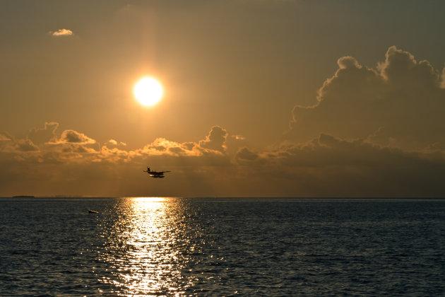 Watervliegtuig landt bij laagstaande zon