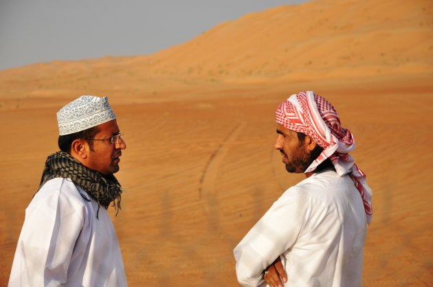 Twee Omani's voeren serieus gesprek midden in de woestijn