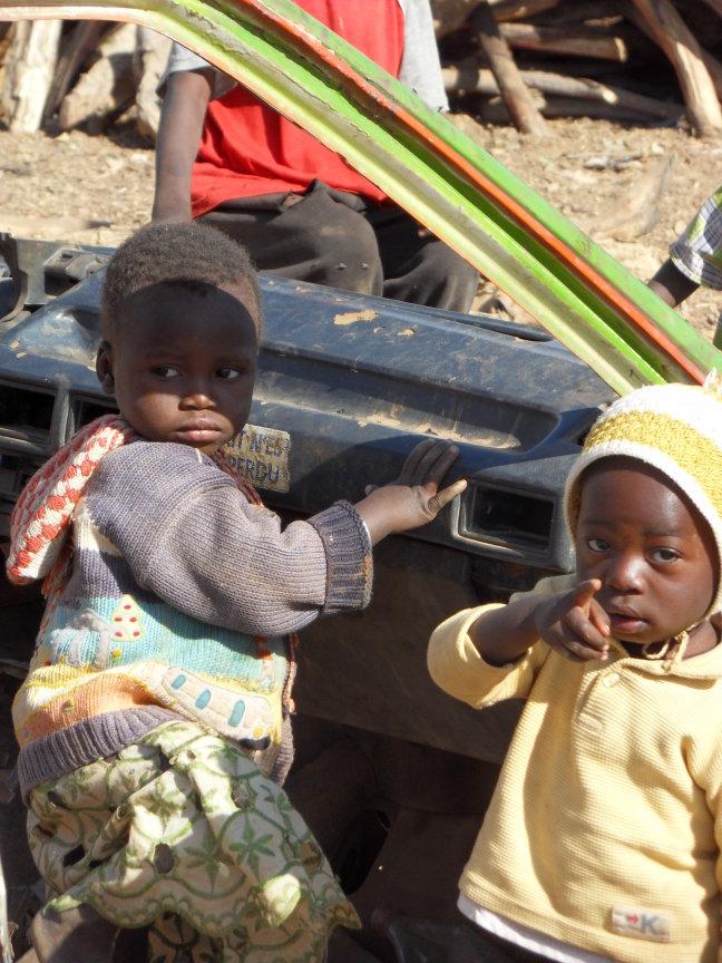 Kinderen spelen in een volledig gestripte taxi in een buitenwijk van Ouagadougou