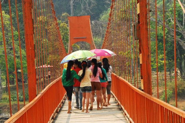 Meisjes met umbrella's op een rode brug