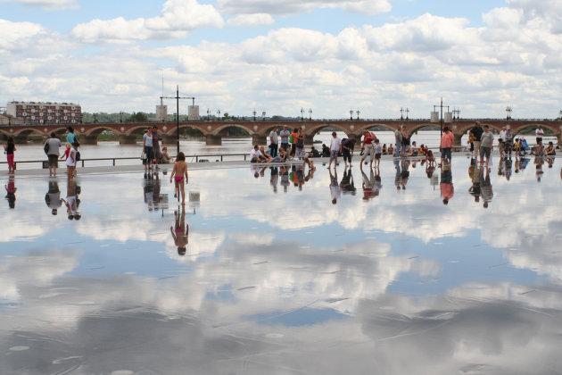 Kinderen spelen op een met water besproeit plein.