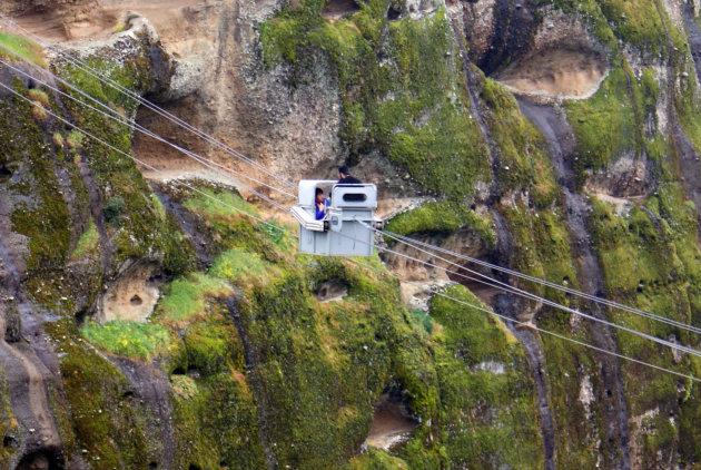 Een priester in een gevaarlijke touw lift bij het Meteora, Griekenland