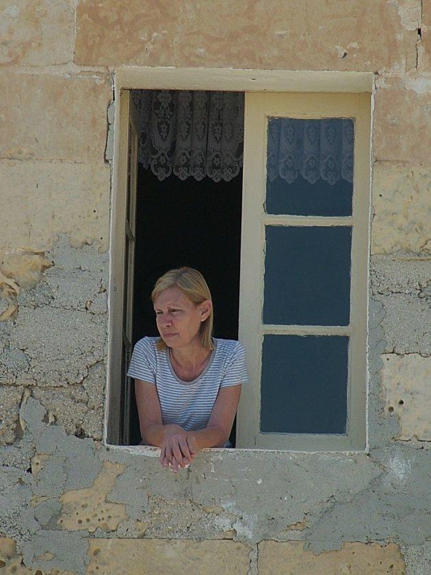 Vrouw kijkend uit een raam