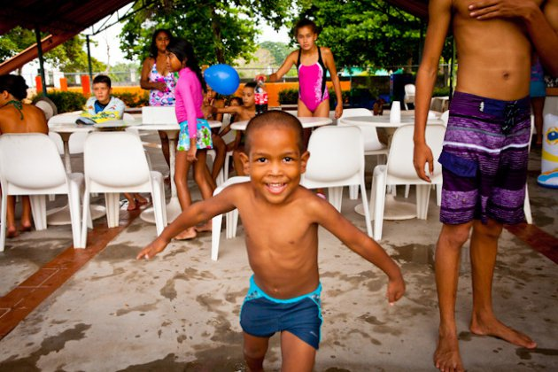 small boy running towards the photographer at a swiming party