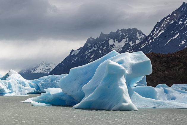 Blokken ijs drijven in het Lago Grey met onheilspellend weer op komst