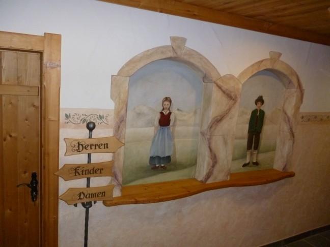 Mooie muurschildering in berghut: Toiletten-wegwijzer