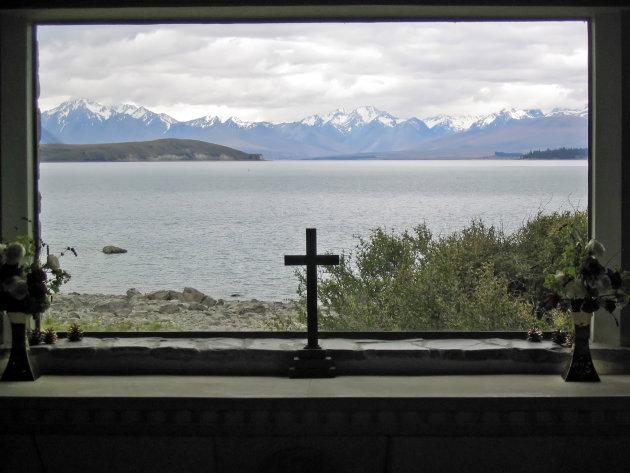 Doorkijkje vanaf kapelletje via Lake Tekapo naar besneeuwde bergen.