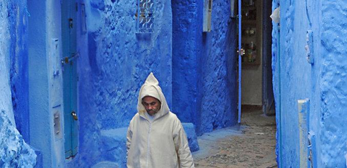 Traditioneel geklede man in blauw straatje te Chefchaouen