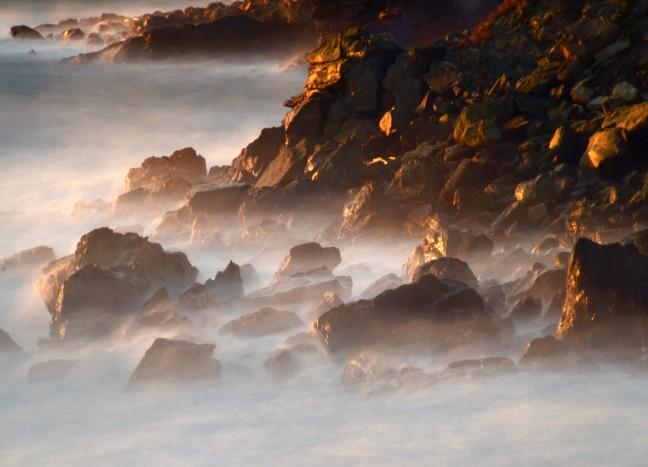 Strandimpressie met verneveld zeewater en laat licht op rotsen.