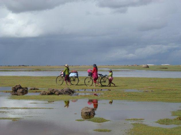 Een Boliviaans gezin op weg naar het dorp in regenseizoen.