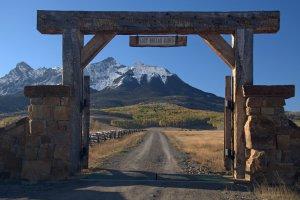 Toegangsweg naar ranch met besneeuwde bergen op achtergrond.