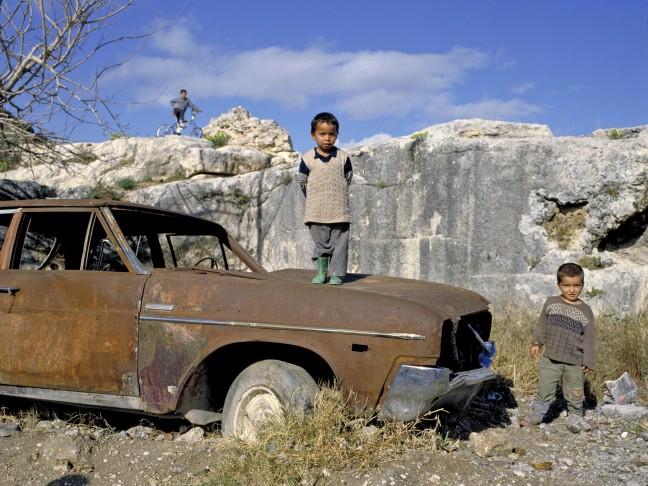 spelend kind staat op oude verroeste auto