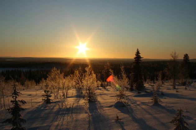 Opkomende zon tijdens een rit met de sneeuwscooter