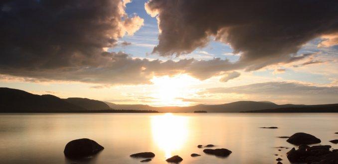 Midzomernacht zon boven meer Karats in Zweeds Lapland.