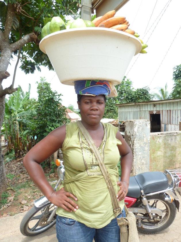 Vrouw lopend door het centrum Sao Tomé stad met fruit.