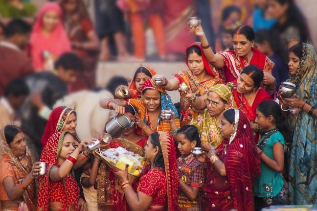 Vrouwen in het rood bij Chhath ceremonie