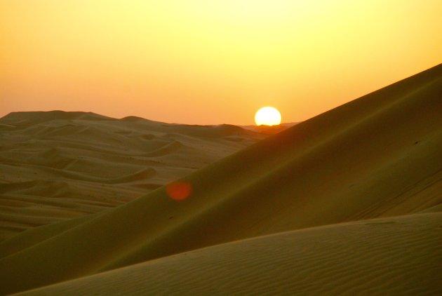 De zon in het zand zien zakken..