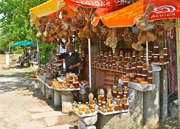 Een honingverkoper bij de ingang van Asklepion.