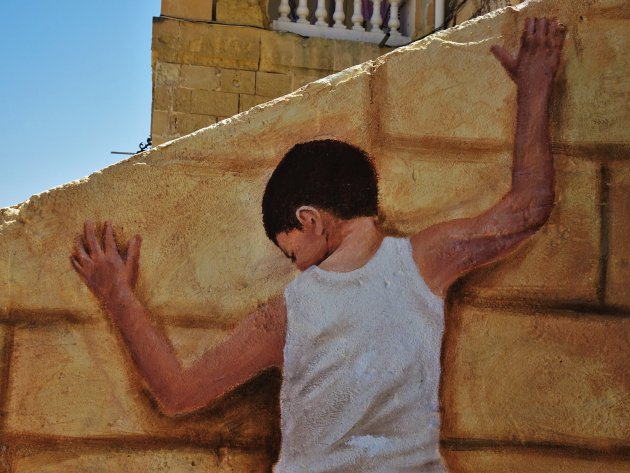 Klimmend jongetje op een muur