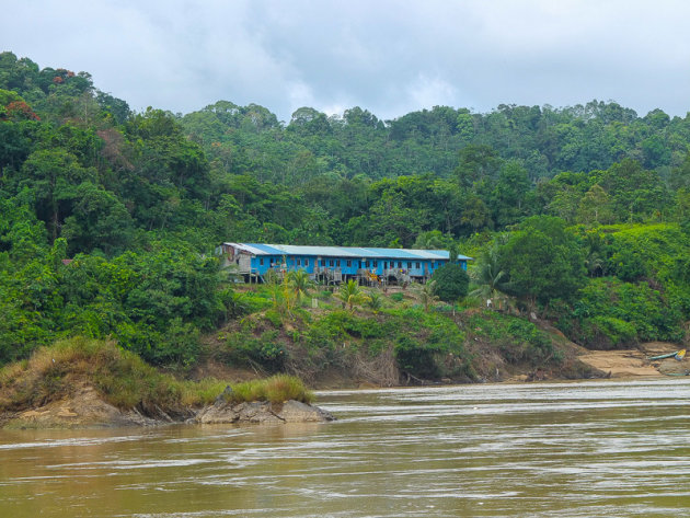 Weg van de bewoonde wereld in Borneo, varen over de rivier langs de longhouses