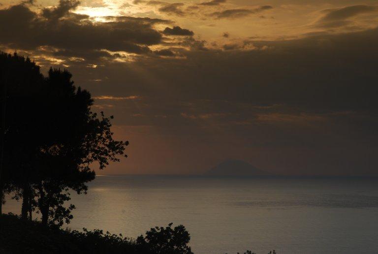 De zee en het spel van licht s'avonds als hij achter de vulkaan