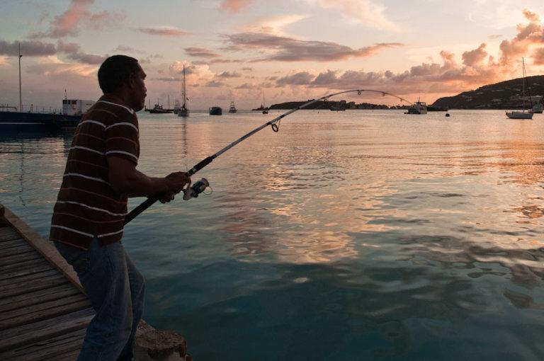 Visser in de haven bij zonsondergang, St Maarten