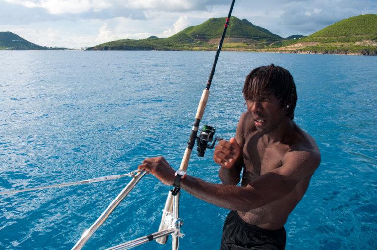 Crew member klimt na een verkoelende duik aan boord van een luxe