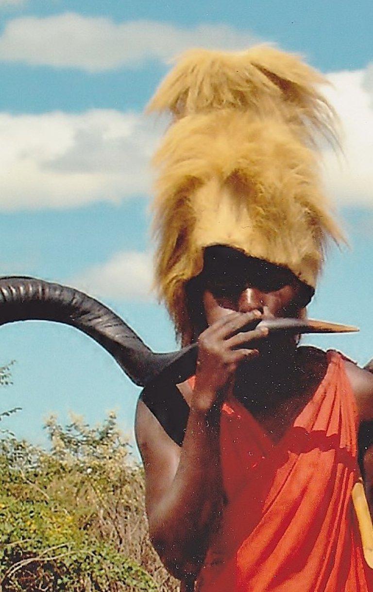 De zoon van het stamhoofd draagt stoer een hoofdtooi van leeuwenmanen. Hij blaast op een buffelhoorn.